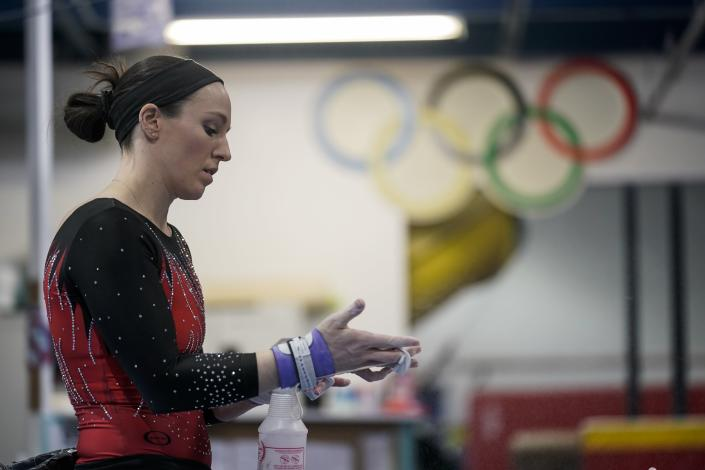 Chellsie Memmel works out Thursday, Feb. 18, 2021, in New Berlin, Wis. Memmel started doing gymnastics again when the COVID-19 pandemic hit last spring because it felt like one of the few things in her life she could control. The 32-year-old former world champion and Olympic silver medalist discovered more than an outlet for stress. (AP Photo/Morry Gash)