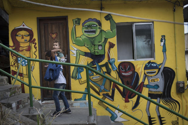 "A boy is carried upstairs along the ""Graffiti Way"" at the Prazeres slum in Rio de Janeiro, Brazil, Friday, March 28, 2014. Dozens of houses were painted by local and international Graffiti artists, creating a colorful path all the way to the top of the community. (AP Photo/Felipe Dana)"