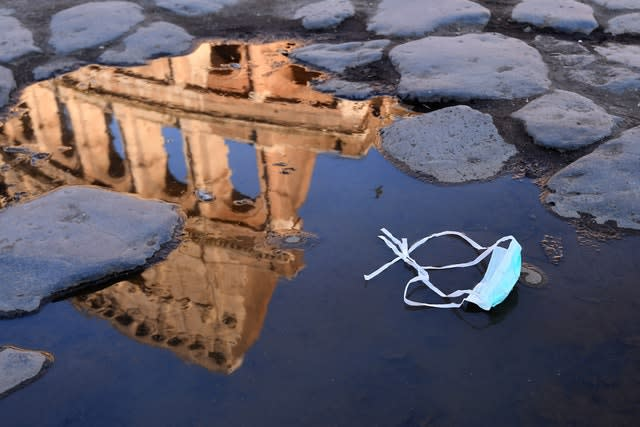 The Colosseum is reflected in a puddle beside a face mask in Rome (AP)