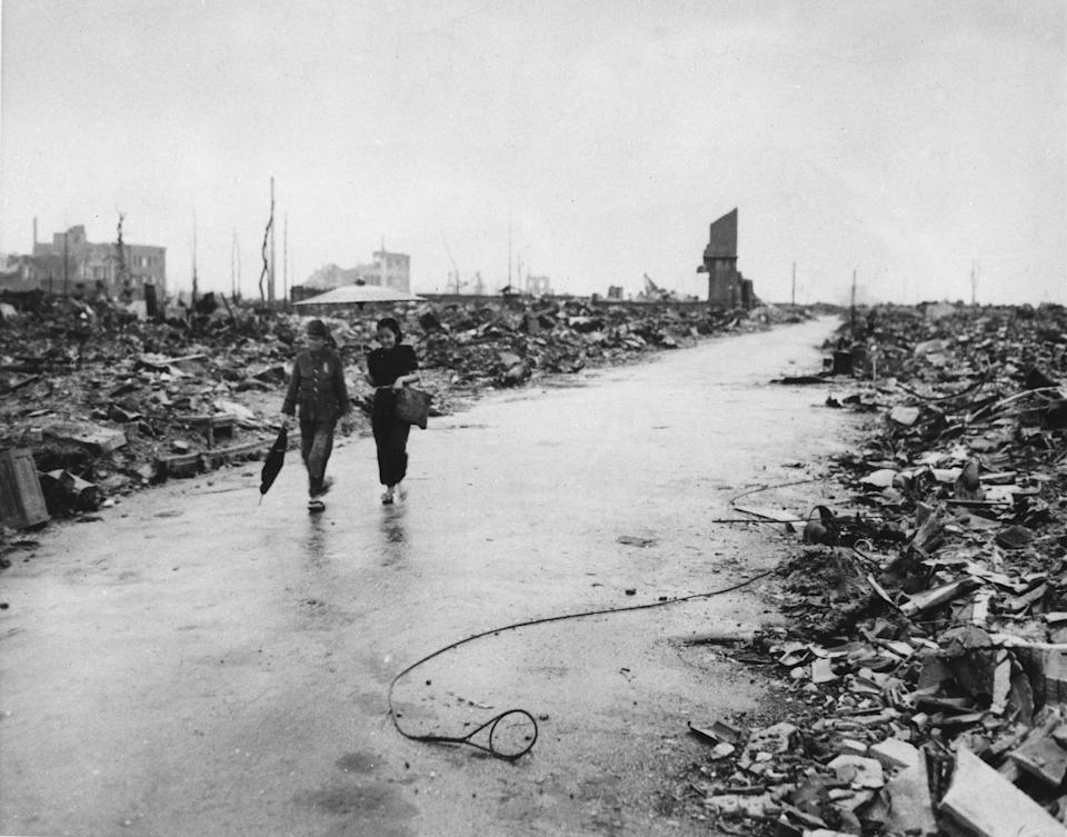 Two people walk on a cleared path through the destruction resulting from the Aug. 6 detonation of the first atomic bomb, Sept. 8, 1945.