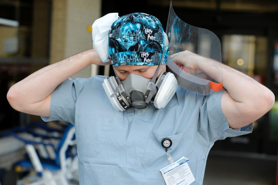 Canadian nurse Steve Homick is photographed  putting on his protective gear outside of the Emergency Entrance before the start of his shift at Beaumont Hospital in Royal Oak, Michigan on April 26, 2020. - The Canada-US border was ordered closed to all non-essential travel in March. Canadian healthcare workers, who are exempt from the travel restriction, are today at the forefront of the fight against the coronavirus in the United States where nearly 70,000 people have died from COVID-19, making it the most infected country in the world. (Photo by JEFF KOWALSKY / AFP) (Photo by JEFF KOWALSKY/AFP via Getty Images)