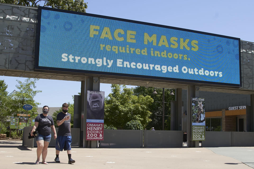 Visitors leave the Henry Doorly Zoo in Omaha, Neb., Monday, July 27, 2020, where face mask wearing is required indoors and encouraged in the outdoor areas. Nebraska's online virus tracker on Monday showed 800 cases were confirmed Friday through Sunday, bringing the state's total to 24,618 since the outbreak began. That included 356 cases confirmed on Friday, 221 on Saturday and 223 on Sunday. (AP Photo/Nati Harnik)
