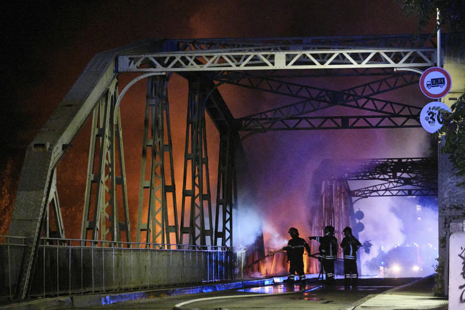 Firefighters work to extinguish flames engulfing the Industry Bridge in Rome, early Sunday, Oct. 3, 2021. A blaze, possibly sparked by a gas canister explosion, destroyed part of an historic bridge spanning the Tiber River in Rome before firefighters extinguished the flames early Sunday. (Mauro Scrobogna/LaPresse via AP)