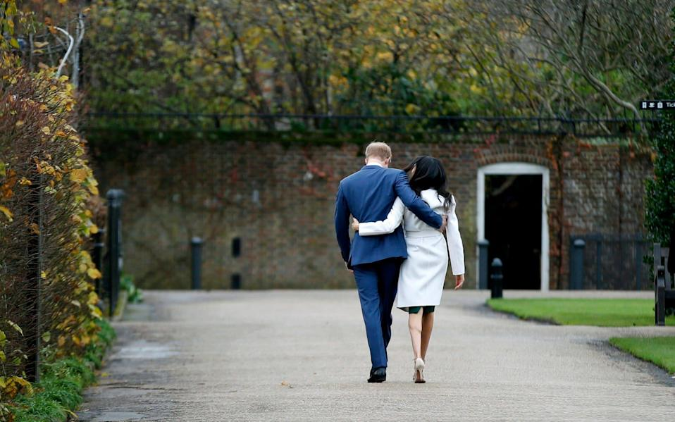 Prince Harry and Meghan Markle walk away after posing for the media in the grounds of Kensington Palace in London - Alastair Grant/AP