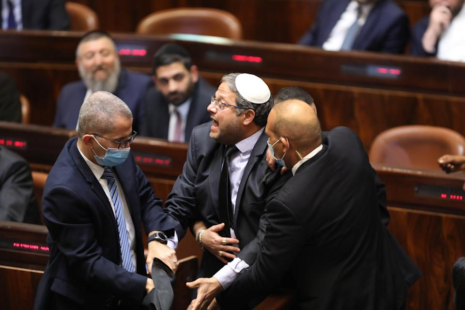 Israeli far right wing Leader of the Jewish home party, Itamar Ben Gvir escorted out by security as he protests during the speech of designated prime minister Naftali Bennett (EPA)