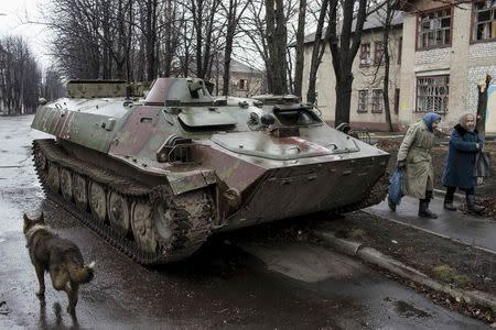 Women walk past destroyed Ukranian army armoured personnel carrier (APS) in the town of Debaltseve, north-east from Donetsk, March 13, 2015. REUTERS/Marko Djurica