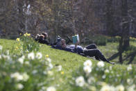 People enjoy the sunny weather in Sefton Park in Liverpool, England, Sunday April 4, 2021. During current coronavirus restrictions people are allowed to meet up and exercise in the open air. (Peter Byrne/PA via AP)