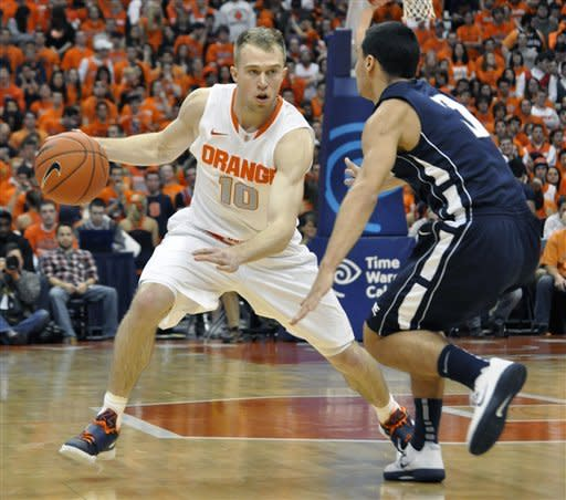 Syracuse's Trevor Cooney drives against Monmouth's Max DiLeo during the first half of an NCAA college basketball game in Syracuse, N.Y., Saturday, Dec. 8, 2012. Syracuse won 108-56. (AP Photo/Kevin Rivoli)