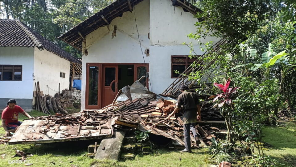 A photo shows people inspect a collapsed house following a 6.0 magnitude earthquake that hit in Blitar, East Java, Indonesia.