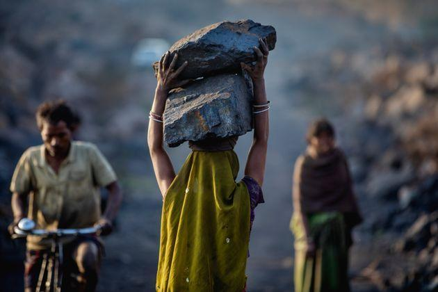 A female worker has piled coal on her head while she is working in Jharia coal field where a large amount of indias coal is mined. (Photo: Jonas Gratzer via Getty Images)