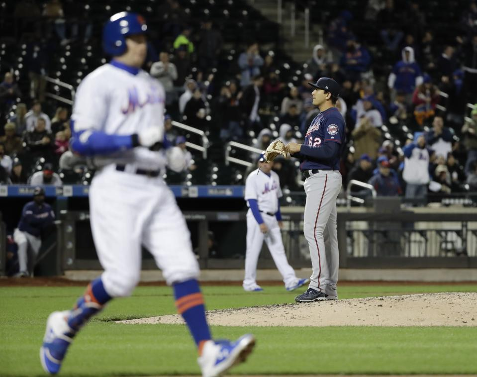 Minnesota Twins' Andrew Vasquez stands on the mound as New York Mets' Brandon Nimmo, left, reaches first base after being hit by a pitch during a baseball game Wednesday, April 10, 2019, in New York. A run scored on the play. (AP Photo/Frank Franklin II)