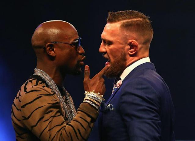 <p>Floyd Mayweather (L) and Conor McGregor talk to each other during the last stop of their four-city, three-country tour. (Getty) </p>