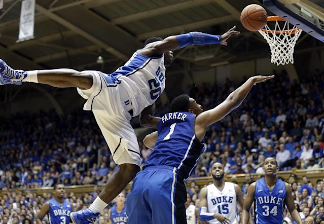 Duke White team's Semi Ojeleye (20) jumps over Blue team's Jabari Parker (1) in the Blue-White scrimmage during the team's Countdown to Craziness NCAA college basketball preseason event in Durham, N.C., Friday, Oct. 18, 2013. (AP Photo/Gerry Broome)