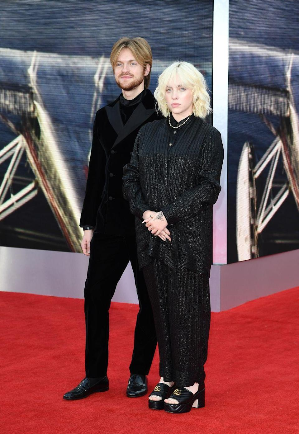 <p>Billie Eilish wore a striped Gucci shirt and trousers with platform shoes to attend the premiere with her brother, Finneas O'Connell, who wore a black velvet Armani suit and a Cartier watch. The pair wrote and performed the film's soundtrack. </p>