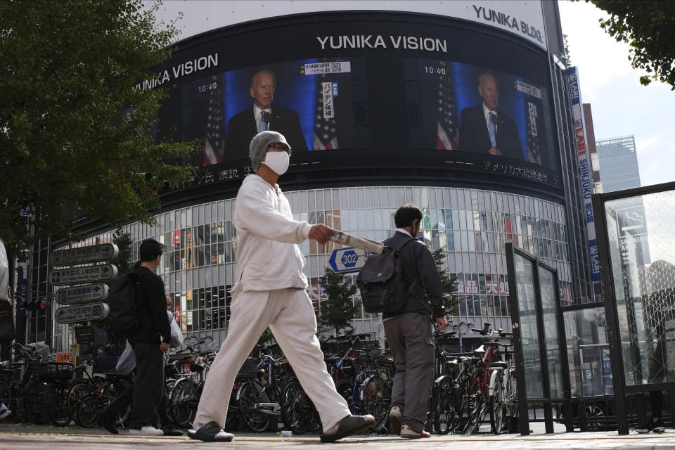A screen shows live broadcast of President-elect Joe Biden speaking Sunday, Nov. 8, 2020 at the Shinjuku shopping district in Tokyo. (AP Photo/Kiichiro Sato)