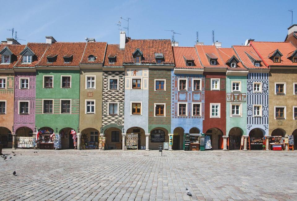 <p>Narrow row houses are broken up with color on the streets of Poznań, Poland.</p>