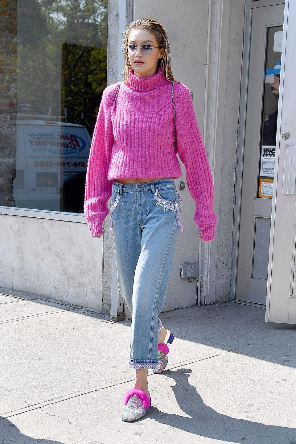 <p>In a hot pink turtleneck sweater, tinted sunglasses, beaded jeans, and pink fur-lined glittery loafers while out in New York.</p>