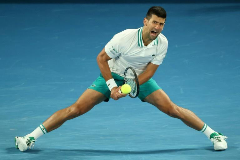 Serbia's Novak Djokovic grimaces as he stretches for a shot during his win against Milos Raonic