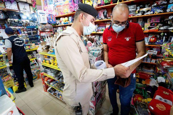 PHOTO: An Iraqi policeman, accompanied by a member of the Interior Ministry's anti-'fake news' team speaks to a toy shop owner distribute a leaflet to spread awareness of the danger and legal consequences spreading fake news in Baghdad, May 20, 2021. (Ahmad Al-rubaye/AFP via Getty Images, FILE)