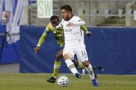 Portland Timbers' Andres Flores (14) dribbles in front of Seattle Sounders' Nouhou in the first half of an MLS soccer match Thursday, Oct. 22, 2020, in Seattle. (AP Photo/Elaine Thompson)
