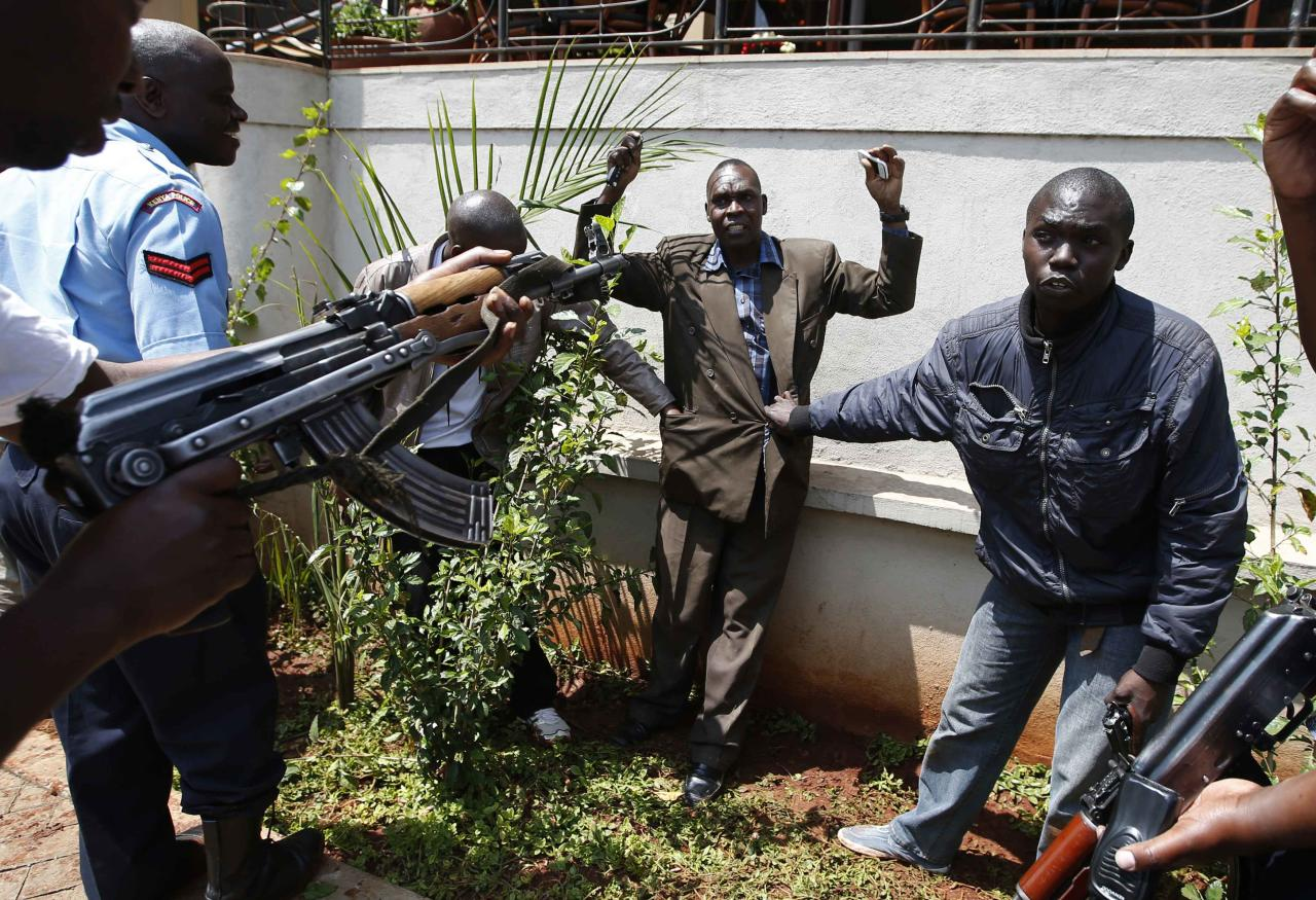 Policemen search a man for weapons as he walked out of Westgate Shopping Centre in Nairobi September 21, 2013. Militant gunmen stormed the shopping mall in Nairobi on Saturday killing at least 39 people, including children, and sending scores fleeing into shops, a cinema and onto the streets in search of safety. Kenyan security forces were still locked in a standoff on Sunday with the al Qaeda-linked militants, who were holding an unknown number of hostages. Picture taken September 21, 2013. REUTERS/Goran Tomasevic (KENYA - Tags: CIVIL UNREST)