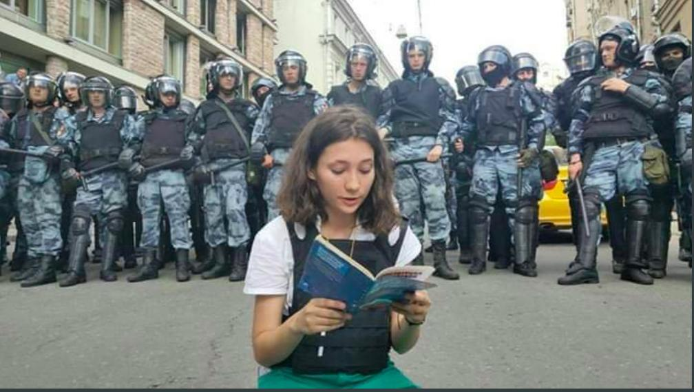 "One of the most defining images of Russia's fight against the Putin administration was that of Olga Misik, the Russian teenager who read the Russian constitution in front of riot police, with netizens likening her to the Tiananmen Square Tank Man. Affirming the right to peaceful protests, the young pro-democracy protestor wanted to let the police know that while they were protesting peacefully, the Russian riot police were with their weapons. The Putin administration has been violently cracking down on people protesting the banning of several leaders of the opposition from contesting in Moscow's City Duma elections, and for greater transparency and political freedom in Russia. <em><strong>Image credit:</strong></em> <a href=""https://twitter.com/joybhattacharj/status/1156767809205968897"">Joy Bhattacharjya/Twitter</a>"