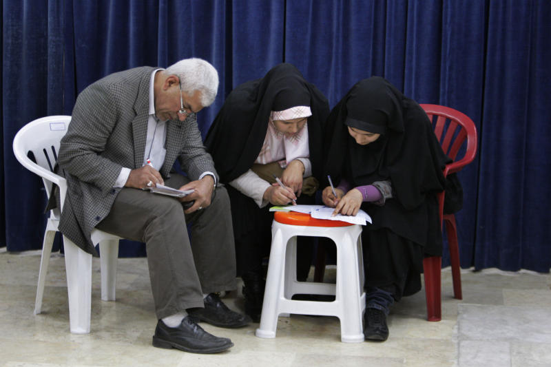 Iranians fill in their ballots for the parliamentary runoff elections, in a polling station, in Tehran, Iran, Friday, May 4, 2012. 130 hopefuls competed for 65 seats in 33 constituencies including the capital Tehran with 25 undecided seats. Conservative opponents of President Mahmoud Ahmadinejad have already won majority of seats of the new parliament in the first round of the elections in March. (AP Photo/Vahid Salemi)