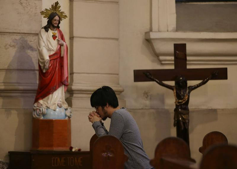"""CORRECTS MONTH - A Filipino Catholic prays beside images of Jesus Christ inside the Our Lady of Remedies Parish Church in Manila, Philippines Sunday, Sept. 22, 2013. Catholics around the globe are expressing mixed but mostly positive reactions to Pope Francis' recent remarks that the church has become too focused on """"small minded rules"""" on hot-button issues like homosexuality and abortion. (AP Photo/Aaron Favila)"""