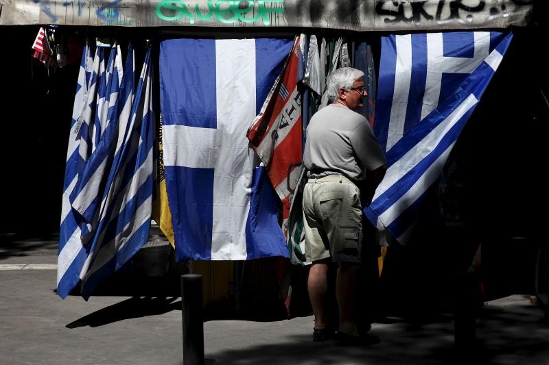 A man stands next to Greek national flag at a kiosk in central Athens