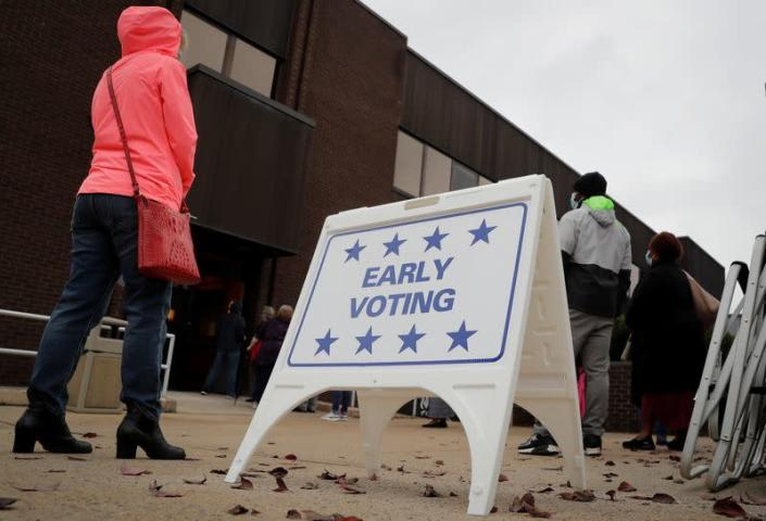 Voters wait in line to cast ballots on the first day of early voting in New York