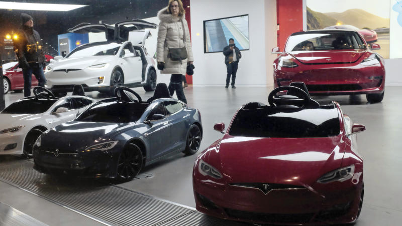 In this Nov. 10, 2018 photo, Tesla Model S, battery operated ride-on cars for children, are displayed by the front window at a Tesla showroom in downtown Chicago. (AP Photo/Kiichiro Sato)