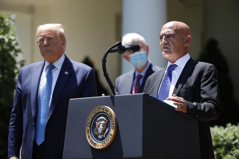 President Donald Trump, left, listens as Moncef Slaoui, a former GlaxoSmithKline executive, speaks about the coronavirus in the Rose Garden of the White House, Friday, May 15, 2020, in Washington. (AP Photo/Alex Brandon)