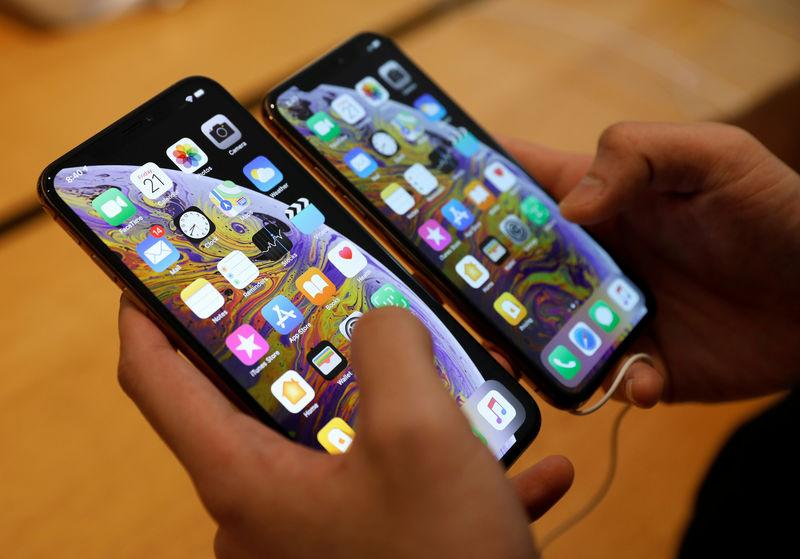 FILE PHOTO: A customer compares the size of the new iPhone XS and iPhone XS Max at the Apple Store in Singapore
