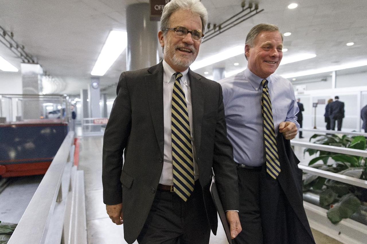 Sen. Tom Coburn, R-Okla., left, walks with Sen. Richard Burr, R-N.C., on the way to a procedural vote on a comprehensive defense bill as the Senate's legislative year nears to a close, at the Capitol in Washington, Thursday, Dec. 19, 2013. (AP Photo/J. Scott Applewhite)