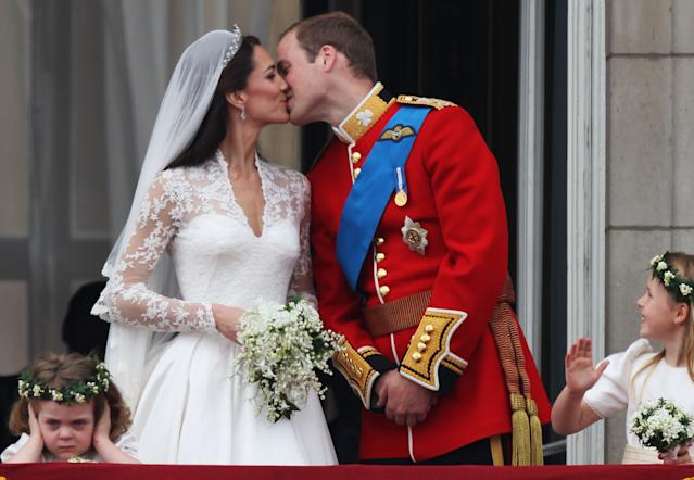 Prince William and Princess Catherine share a kiss from the balcony at Buckingham Palace on their wedding day April 29, 2011 in London, England.