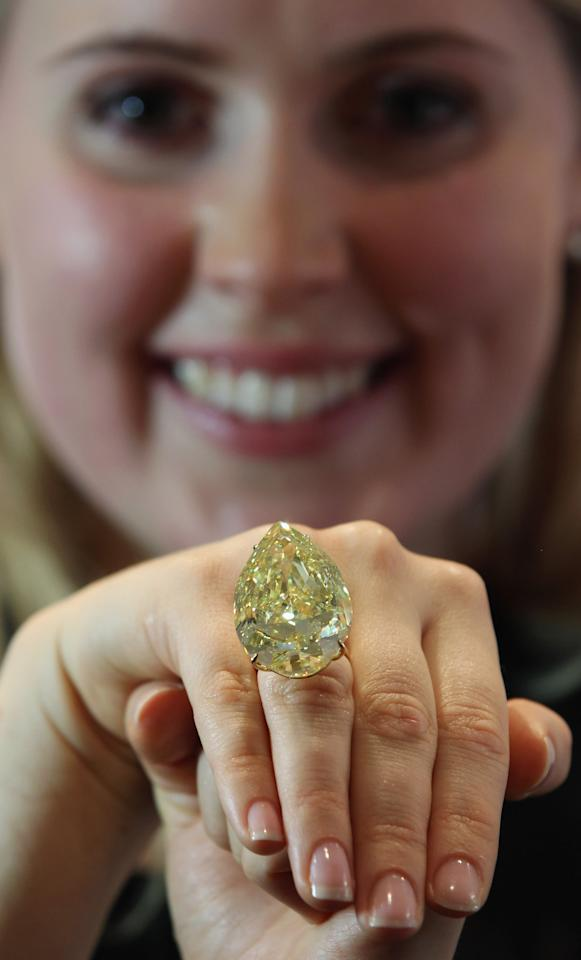 LONDON, ENGLAND - OCTOBER 24:  A Sotheby's employee holds a 110.03 carat sun-drop diamond on October 24, 2011 in London, England. The diamond is the largest yellow pear-shaped diamond in the world, and is expected to fetch between $11-15 Million USD when it is sold at auction at Sotheby's Auction house in London.  (Photo by Dan Kitwood/Getty Images)