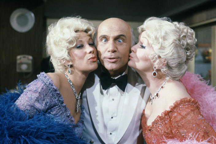 """FILE - In this Oct. 15, 1982 file photo shows Gavin MacLeod with actress Debbie Reynolds and Marilyn Michaels on the set of """"The Love Boat."""" Gavin MacLeod has died. His nephew told the trade paper Variety that MacLeod died early Saturday, May 29, 2021. (AP Photo/Doug Pizac, File)"""