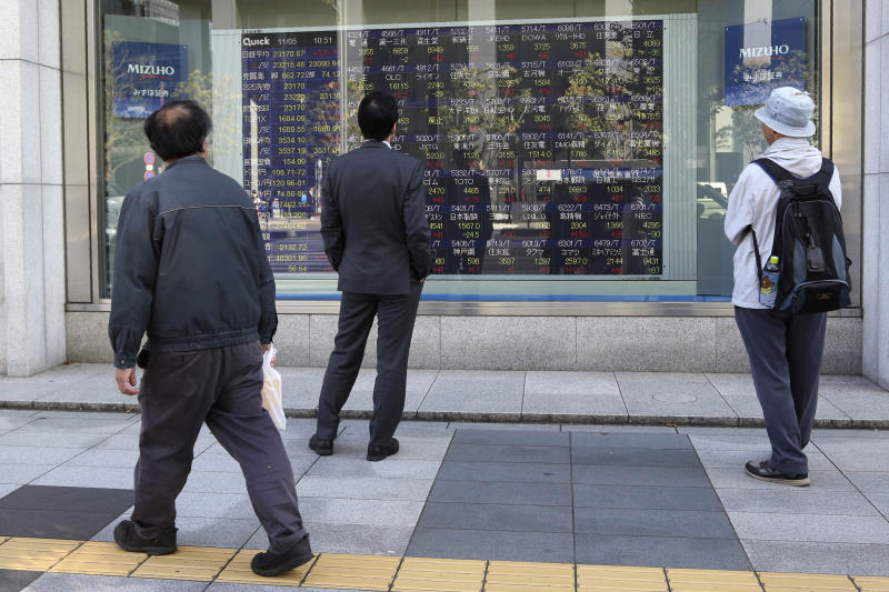 In this Tuesday, Nov. 5, 2019, photo, people look at an electronic stock board of a securities firm in Tokyo. Asian stock markets were mixed Wednesday, Nov. 6, 2019, after investors were rattled by a possible snag in a U.S.-Chinese trade truce following reports Beijing wants Washington to life punitive tariffs. (AP Photo/Koji Sasahara)