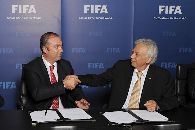A photo released by FIFA shows Cyprus Turkish Football Association President Hasan Sertoglu (L) and Cyprus Football Association President Costakis Koutsokoumnis shaking hands on November 5, 2013 in Zurich (AFP Photo/)