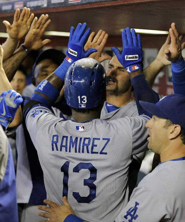 Los Angeles Dodgers' Hanley Ramirez (13) is greeted in the dugout after hitting a three-run home run against the Arizona Diamondbacks during the third inning of a baseball game on Thursday, Sept. 19, 2013, in Phoenix. (AP Photo/Matt York)