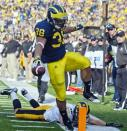 Michigan running back Thomas Rawls (38) avoids a tackle from Iowa cornerback Micah Hyde (18) and leaps over the goal line pylon in an attempt to score a touchdown in the second quarter of an NCAA college football game, Saturday, Nov. 17, 2012, in Ann Arbor, Mich. Rawls was ruled out of bounds at the two-yard line. (AP Photo/Tony Ding)