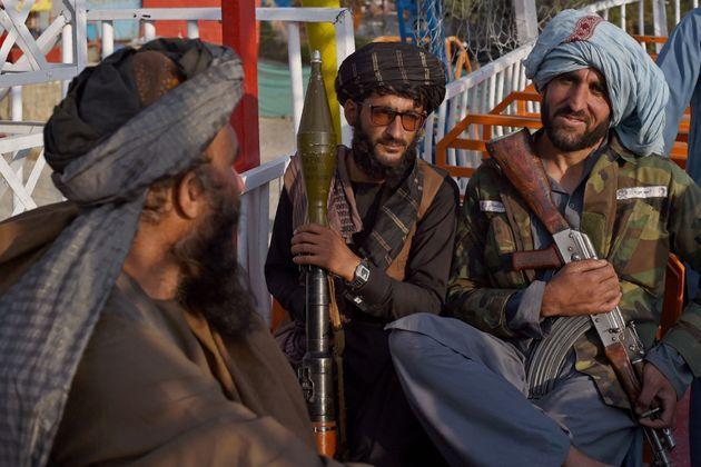 In this photograph taken on September 28, 2021 Taliban fighters enjoy a ride on a pirate ship attraction in a fairground at Qargha Lake on the outskirts of Kabul. -