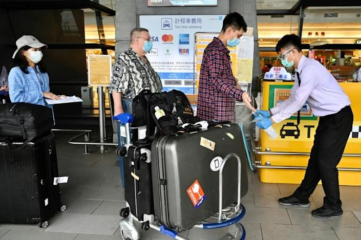 A worker sprays hand sanitiser onto passengers after they arrived at Taoyuan Airport. Taiwan has gained plaudits for its response to the coronavirus outbreak (AFP Photo/Sam Yeh)