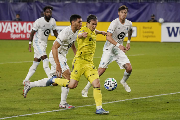 Nashville midfielder Alex Muyl, foreground, shoots in front of Minnesota United defenders during the first half of an MLS soccer match Tuesday, Oct. 6, 2020, in Nashville, Tenn. (AP Photo/Mark Humphrey)