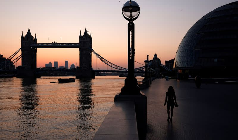 A woman walks near City Hall and Tower Bridge at dawn in London