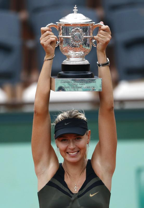 Russia's Maria Sharapova holds a trophy on the podium after winning against Italy's Sara Errani their Women's Singles final tennis match of the French Open tennis tournament at the Roland Garros stadium, on June 9, 2012 in Paris.   AFP PHOTO / THOMAS COEXTHOMAS COEX/AFP/GettyImages