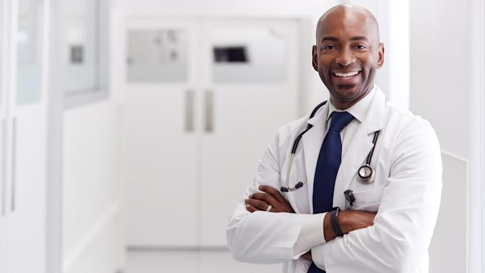 Portrait Of Mature Male Doctor Wearing White Coat Standing In Hospital Corridor.