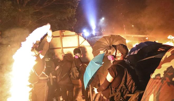 A protester hurls a petrol bomb in a clash with riot police on the Chinese University campus. Photo: Felix Wong
