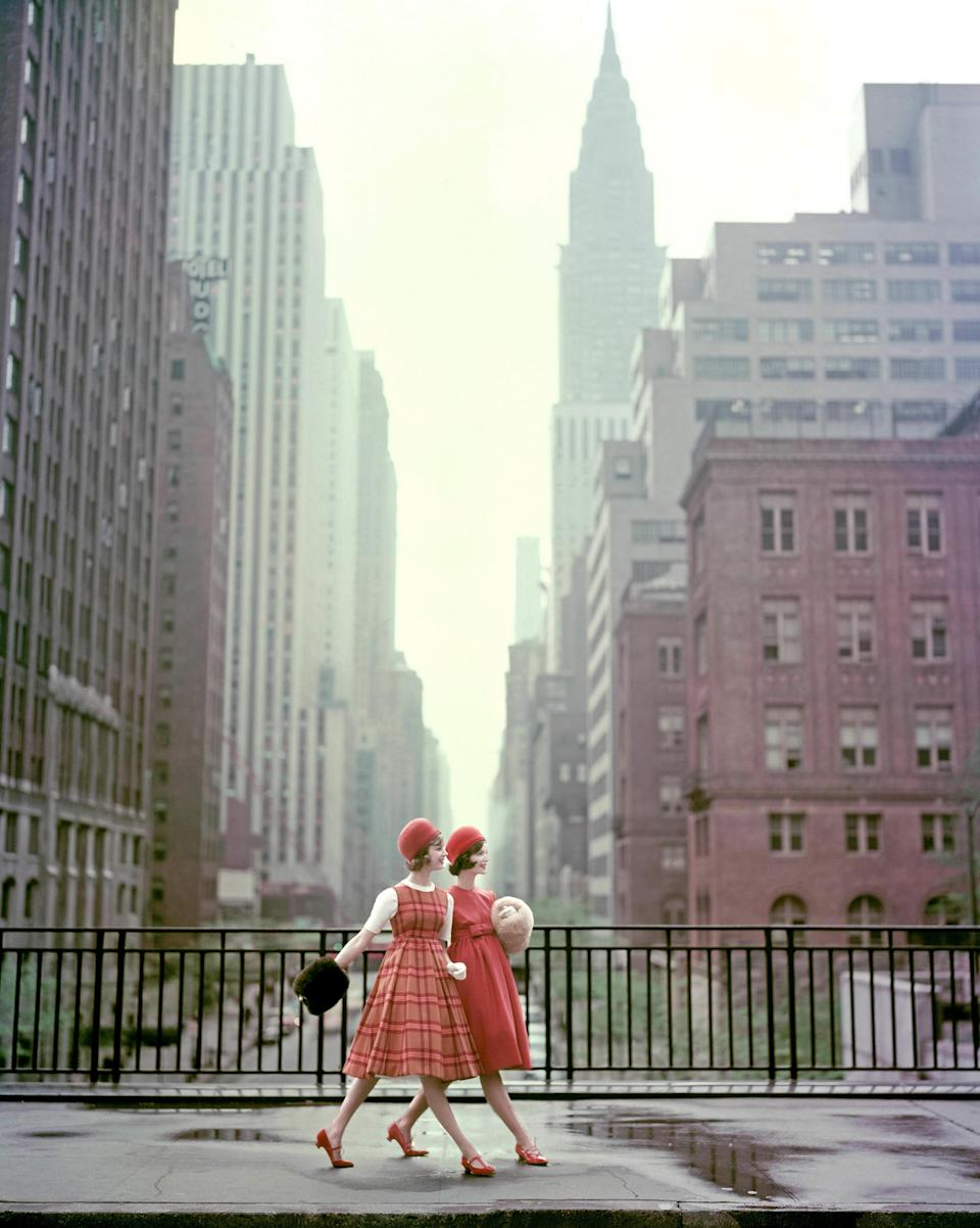 Two models wearing fur muffs, velvet dome hats, and baby-waist dresses pose in front of the Chrysler Building during a photoshoot for <em>Vogue</em>.