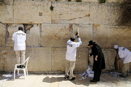 Men, including Western Wall Rabbi Shmuel Rabinowitz, clear notes placed in the cracks of the Western Wall, Judaism's holiest prayer site, to create space for new notes ahead of the Jewish holiday of Passover, in Jerusalem's Old City, March 20, 2018. REUTERS/Ammar Awad